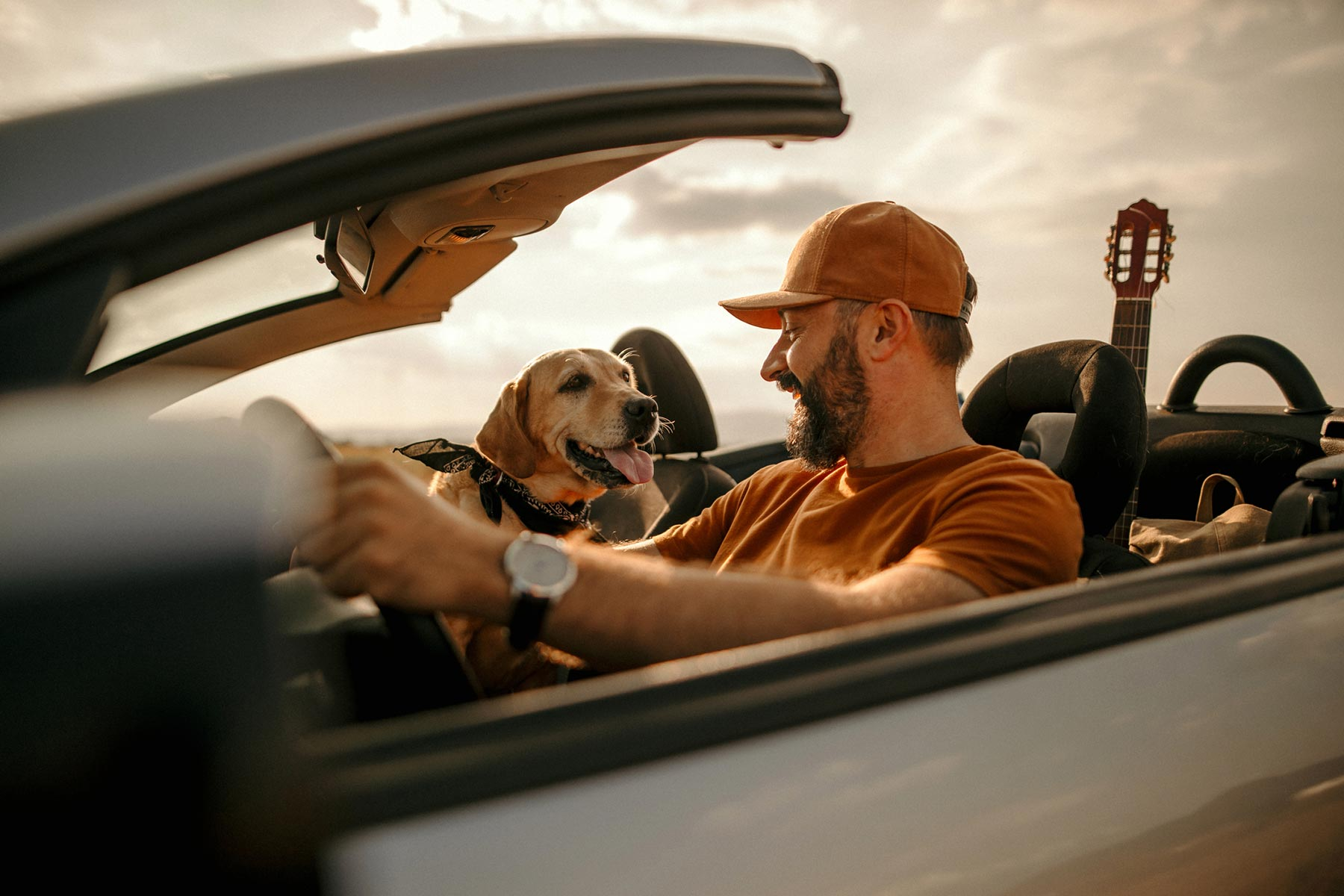 man with guitar and dog in car