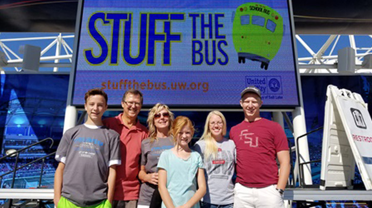 group of people in front of Stuff the bus sign